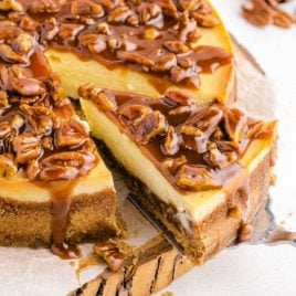 pecan pie cheesecake topped with caramel and pecans on a wooden board