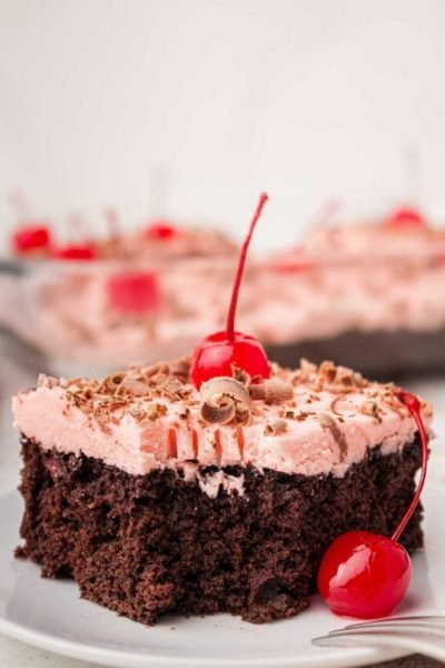 close up shot of a slice of Cherry Dr. Pepper Cake topped with a cherry