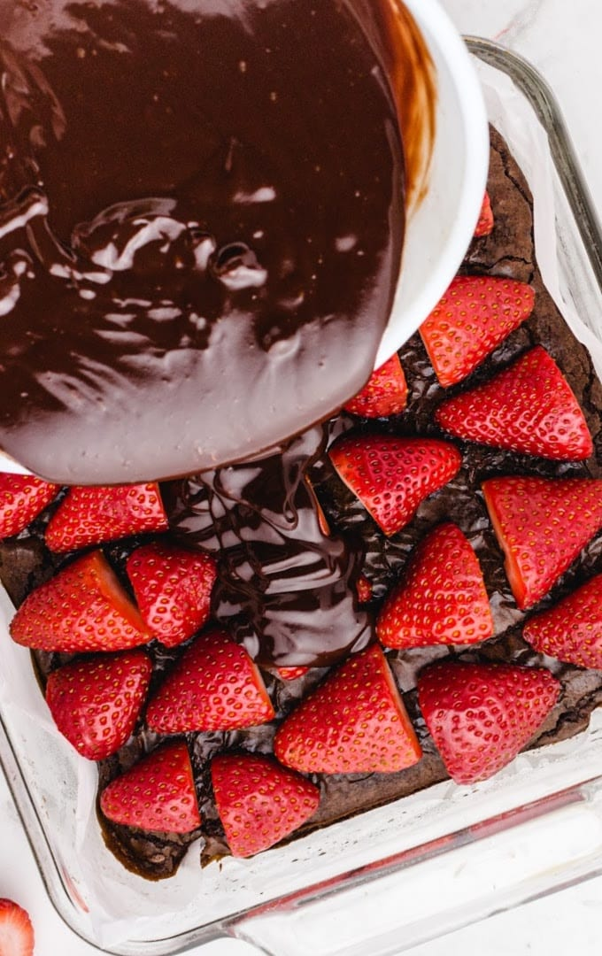 close up of Chocolate Covered Strawberry Brownies with chocolate being poured