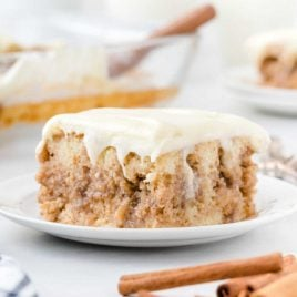 close up shot of a slice of cinnamon roll poke cake on a plate