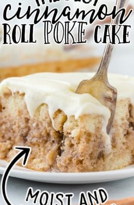 close up shot of a slice of cinnamon roll poke cake being cut with a spoon