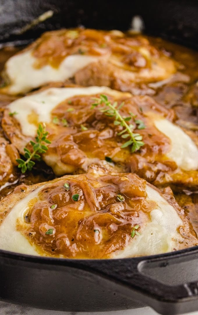 close up shot of French onion pork chops in a dish with cheese and sauce on top