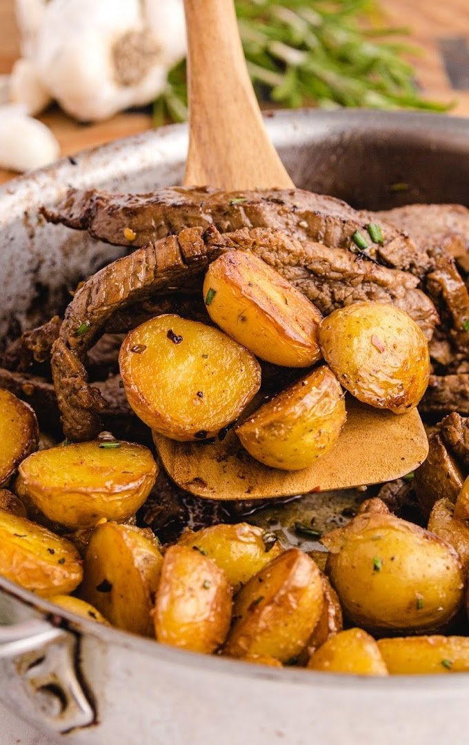 close up overhead shot of garlic butter steak and potato skillet in a dish