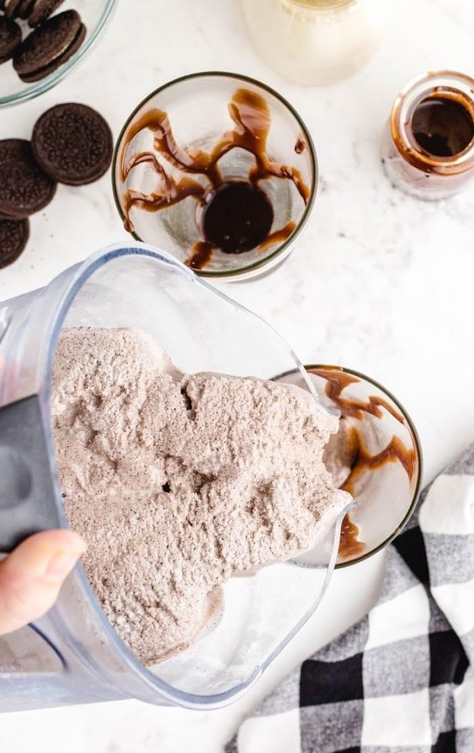 Oreo milkshake shot of ingredients being poured in cup