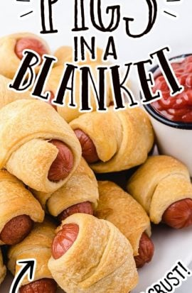 close up shot of pigs in a blanket on a white plate with dipping sauce