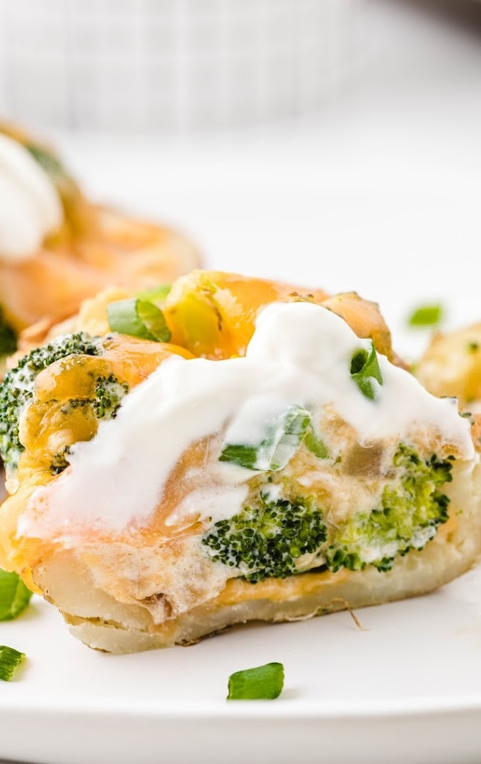 close up shot of broccoli and cheddar potato skins on a white plate