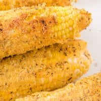 close up shot of fried corn on the cob piled on top of eachother