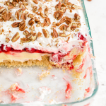 close up shot of cherry cheesecake lush in a clear baking pan