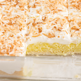 close up shot of coconut cream bars in a clear dish