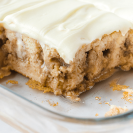 close up shot of cinnamon roll poke cake sliced in a clear dish