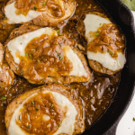 close up overhead shot of French onion pork chops in a dish with cheese and sauce on top