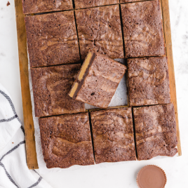 close up shot of chocolate peanut butter brownies on a wooden board