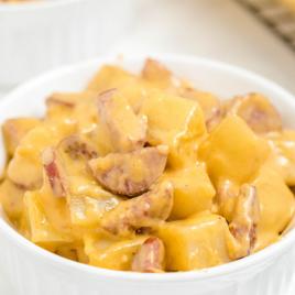 close up shot of kielbasa and potato bake in a white bowl
