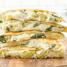 close up shot of spinach artichoke quesadillas on a wooden board