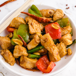 close up shot of Kung Pao chicken on a white plate