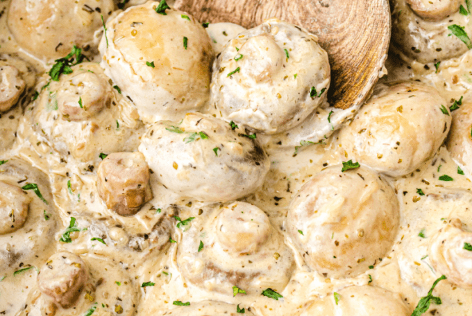 close up shot of garlic parmesan mushrooms with sauce being picked up with a wooden spoon