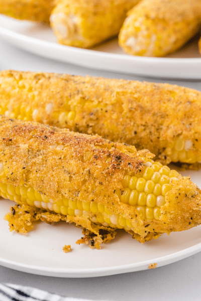 close up shot of fried corn on the cob on a white plate
