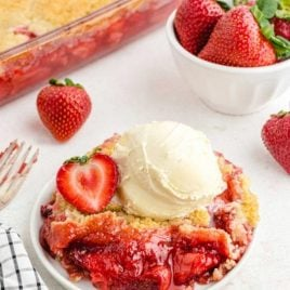 strawberry cobbler on a white plate topped with a slice of strawberry and vanilla ice cream