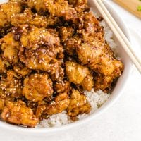 close up shot of sesame chicken served over white rice in a bowl