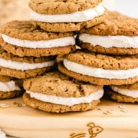 close up side shot of oatmeal cream pies stacked on top of each other on a board