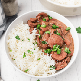 red beans and rice garnished with green onions in a white bowl