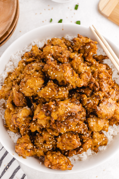 close up overhead shot of sesame chicken served over white rice in a bowl