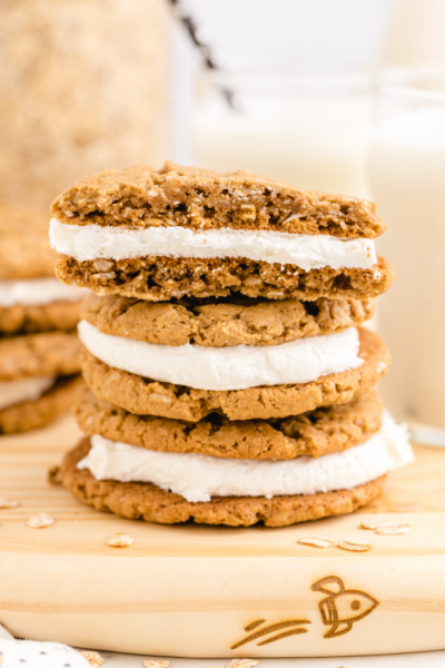 side shot of oatmeal cream pies stacked on top of each other on a board with a piece taken out of the top pie