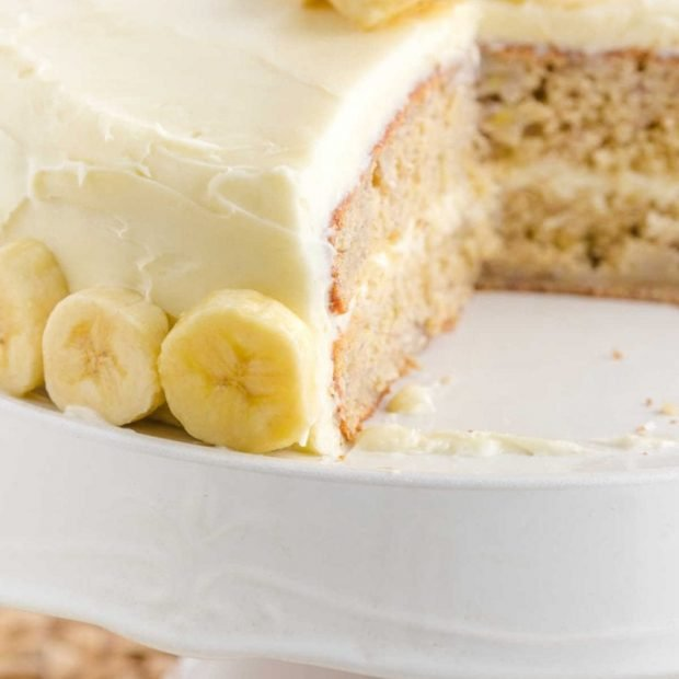close up shot of Banana Cake topped with slices of bananas on a cake serving dish