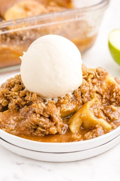 close up side shot of apple crisp topped with vanilla ice cream on a white plate