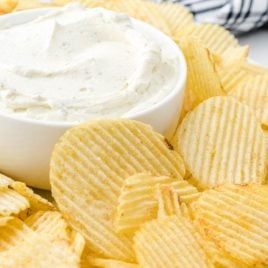 close up side shot of chip dip served with chips on a plate