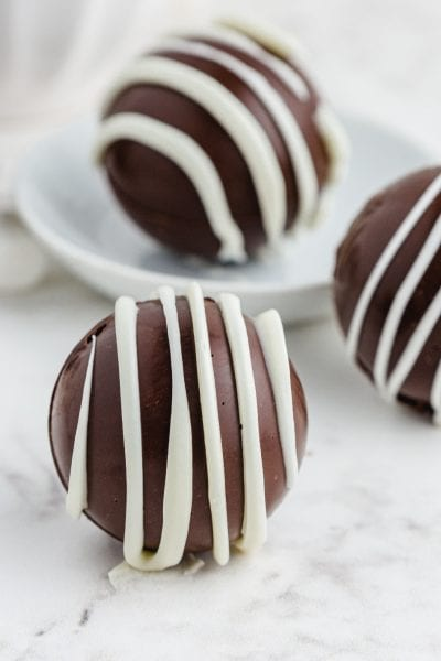 close up of Hot Chocolate Bombs drizzled with white chocolate