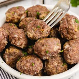 close up shot of homemade meatballs stacked in a bowl and being picked up with a fork