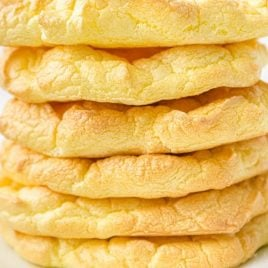 close up shot of cloud bread stacked on top of each other on a white plate