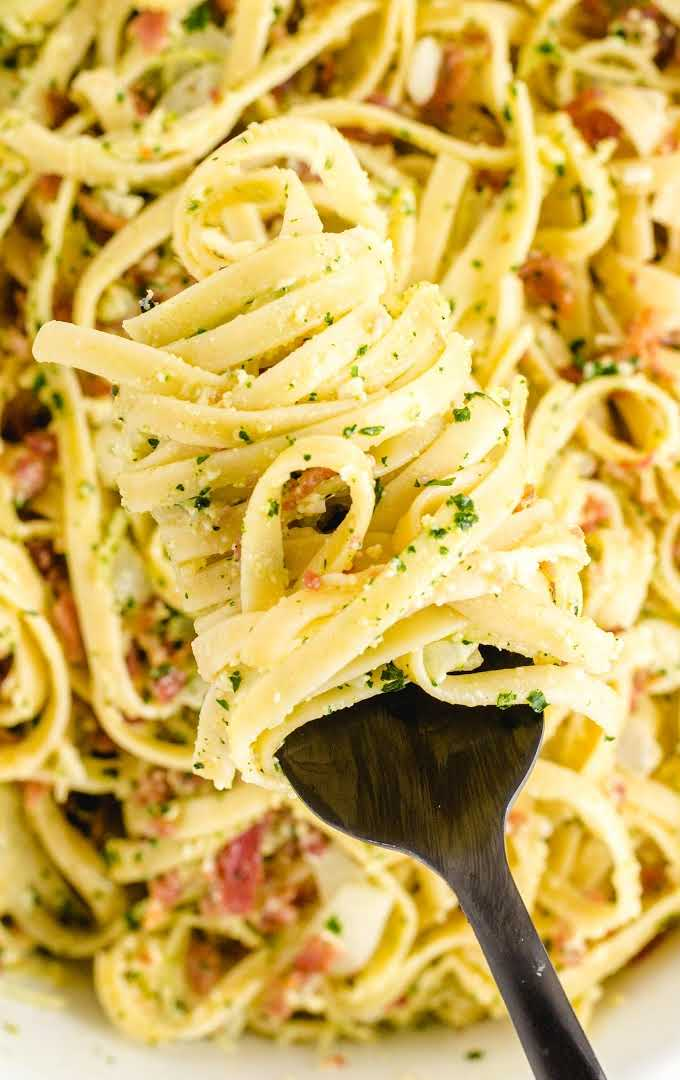 close up overhead shot of carbonara pasta in a white bowl being picked up with a fork