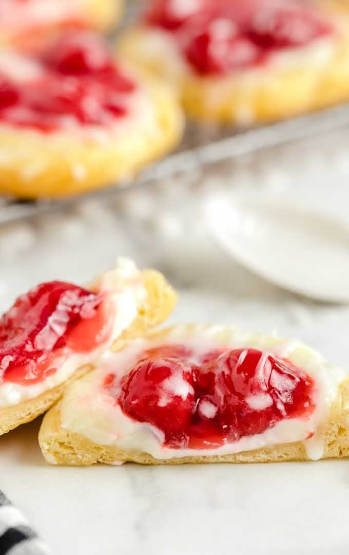 cherry danish with icing on top stacked on top of each other