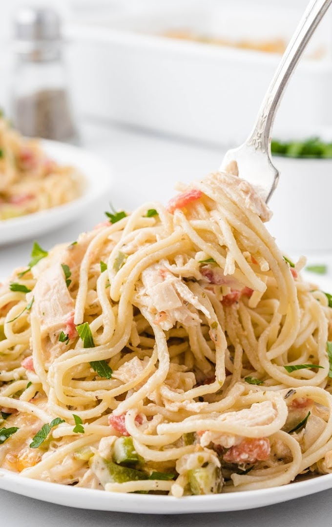 chicken spaghetti on a plate garnished with herbs being picked up with a fork