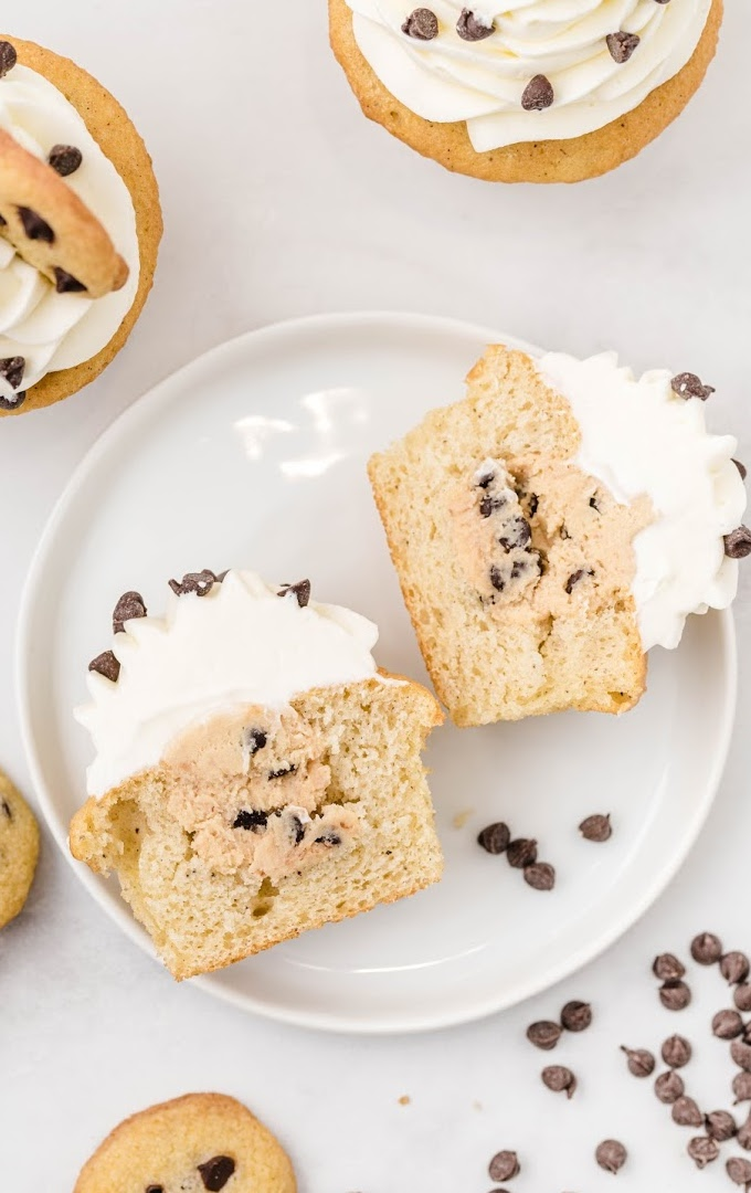 close up overhead shot of cookie dough cupcakes sliced in half on a white plate