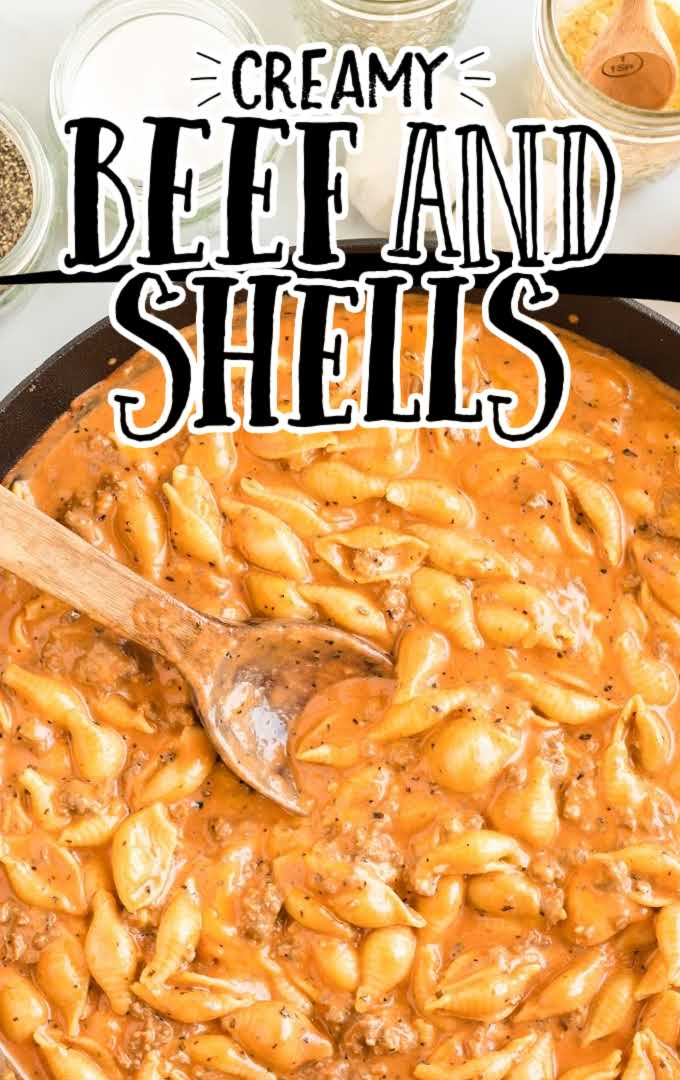 overhead shot of creamy beef and shells in a pan with a wooden spoon