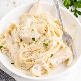 close up shot of a bowl of Creamy Italian Chicken with Pasta garnished with parsley