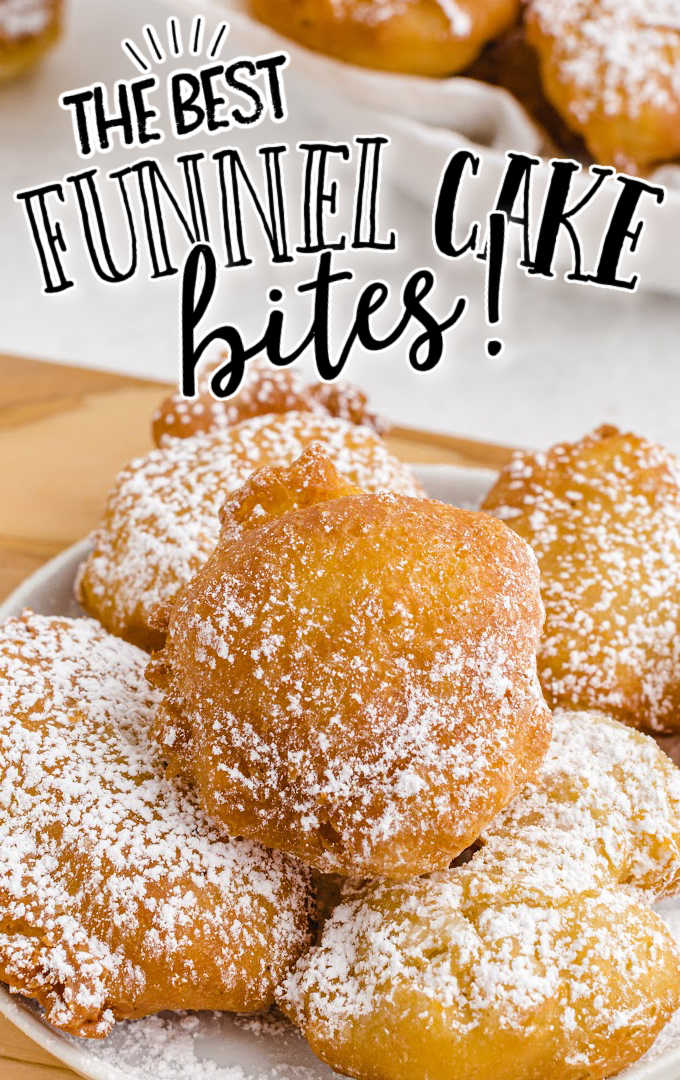 close up shot of funnel cake bites sprinkled with powdered sugar on a white plate