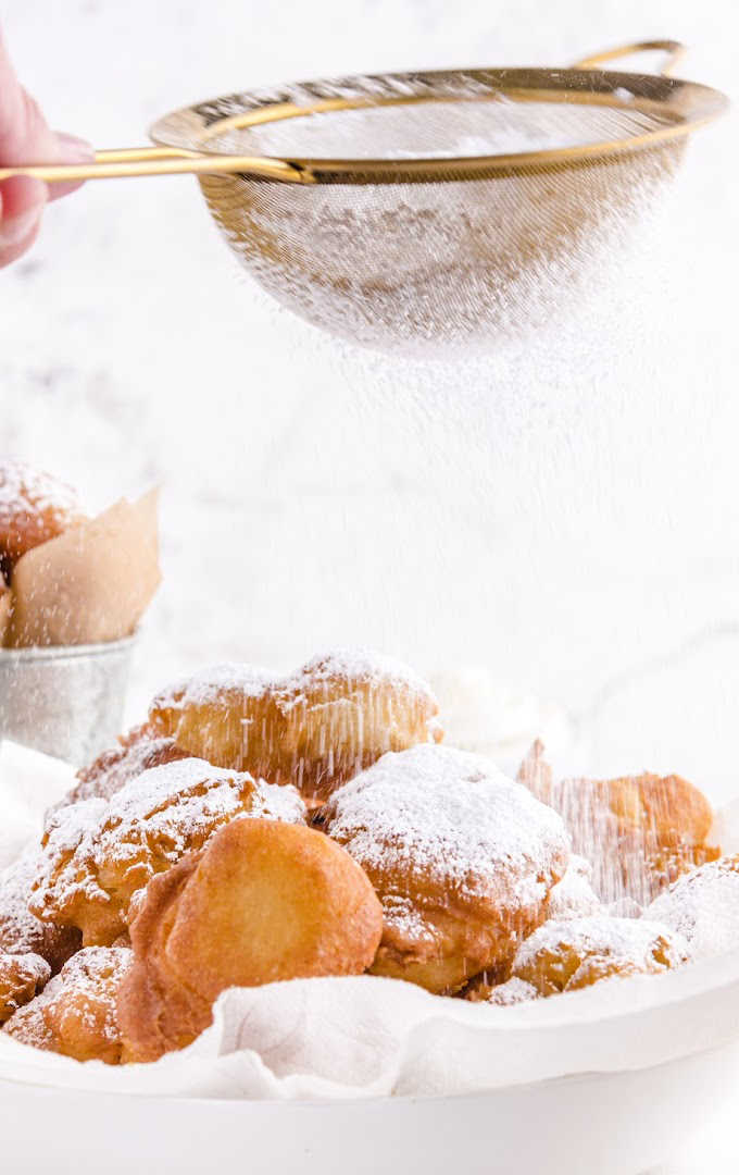 funnel cake bites on a white plate with powdered sugar being sprinkled on it`