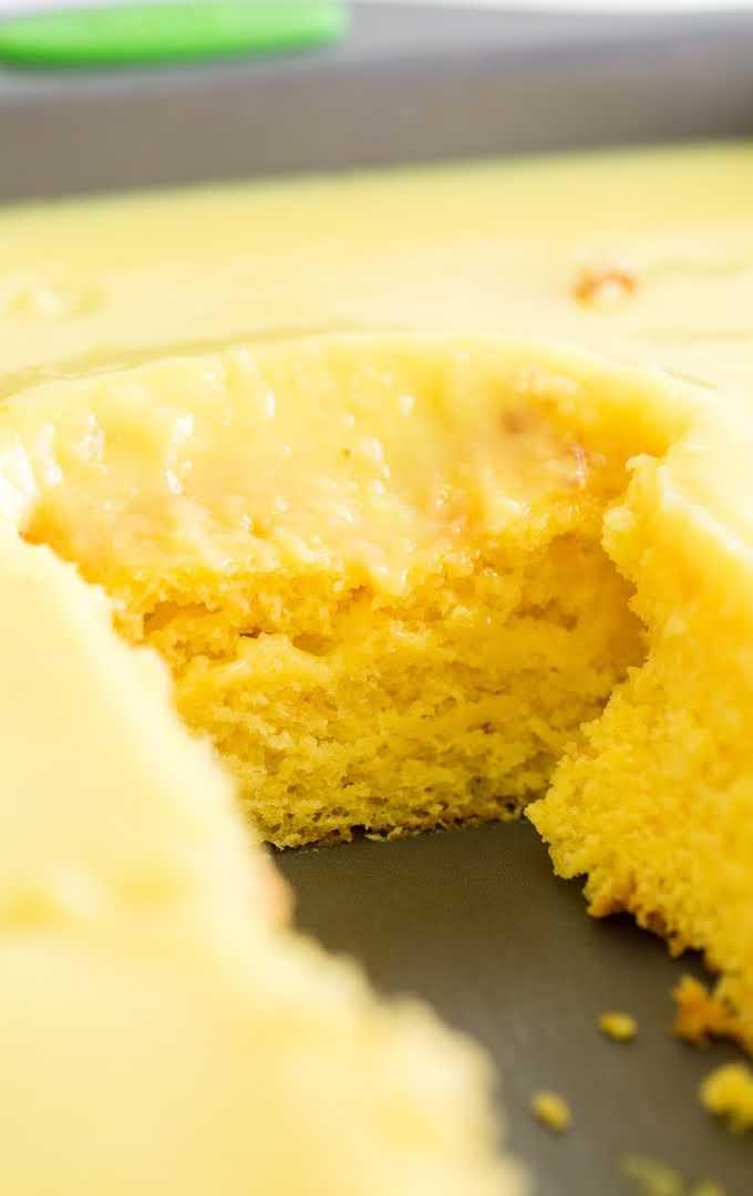 lemon poke cake in a pan with a slice taken off of it