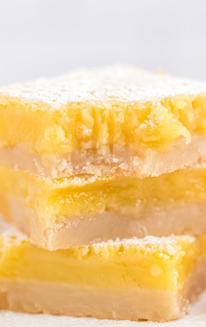 close up side shot of lemon cheesecake bars stacked on top of each other