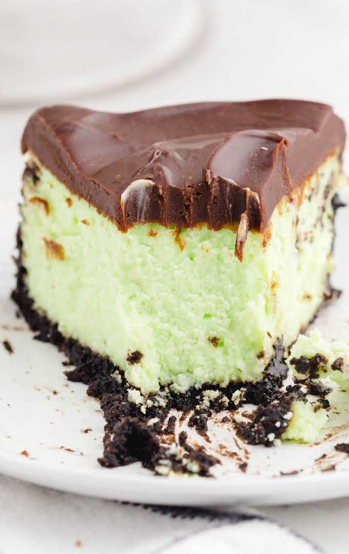 close up front shot of mint chocolate cheesecake with a piece taken out of it with a fork on a plate