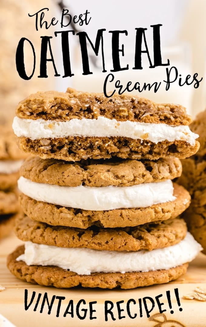 close up side shot of oatmeal cream pies stacked on top of each other on a board with a piece taken out of the top pie