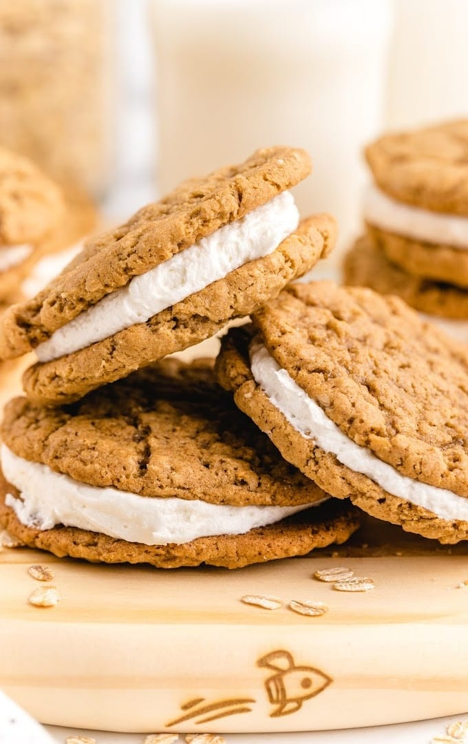 close up shot of oatmeal cream pies piled on top of each other on a wooden board