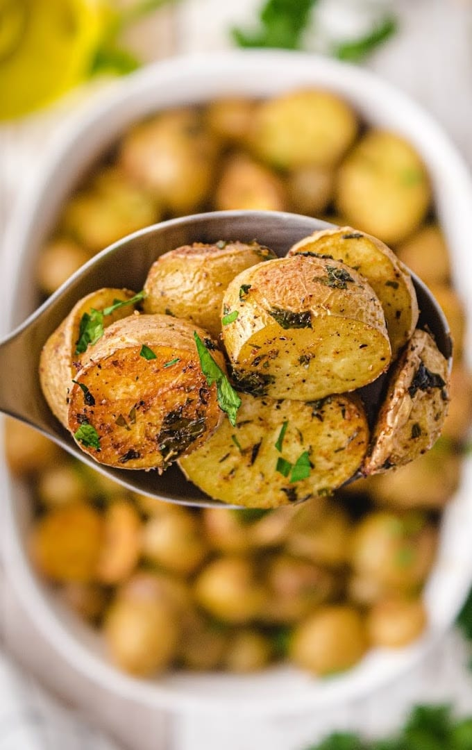 close up shot of oven roasted potatoes being picked up in a spoon