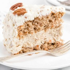 close up side shot of carrot cake cheesecake slice on a white plate with a fork