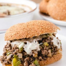 close up shot of philly cheesesteak sloppy joes with provolone and green peppers on buns