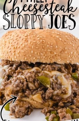 close up shot of Philly cheesesteak sloppy joes oozing out on a white plate